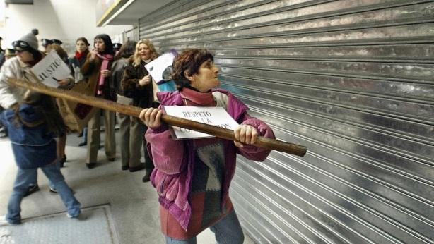 A protester strikes the blind of the Galicia Bank